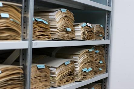 Piles of paper in an a grey office bookshelf