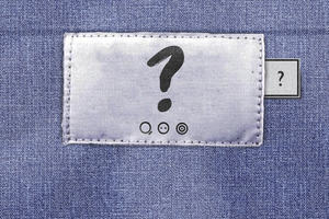 Clothing label bearing a question mark, three wash symbols with the text 'be curious', 'find out', and 'do something'. A Fashion Revolution tab appears to the right of the main label.