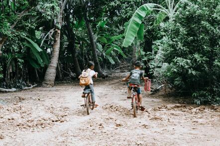 Children riding bikes to school through a jungle path.