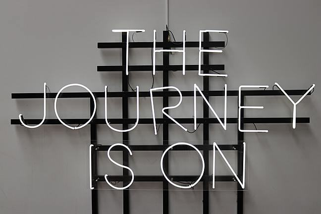 White writing on black hatched background led sign - the journey is on