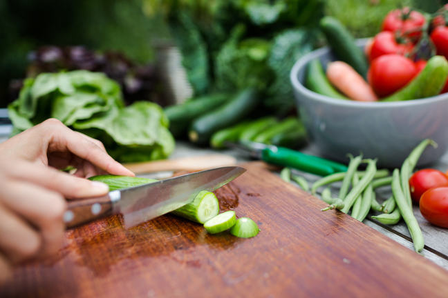 Cutting fresh vegetables on chopping board