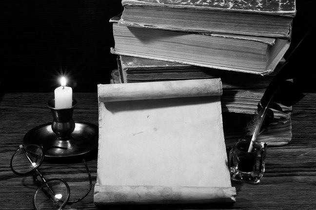 Pile of books on a table with quill and ink bottle, parchment, candle and reading spectacles