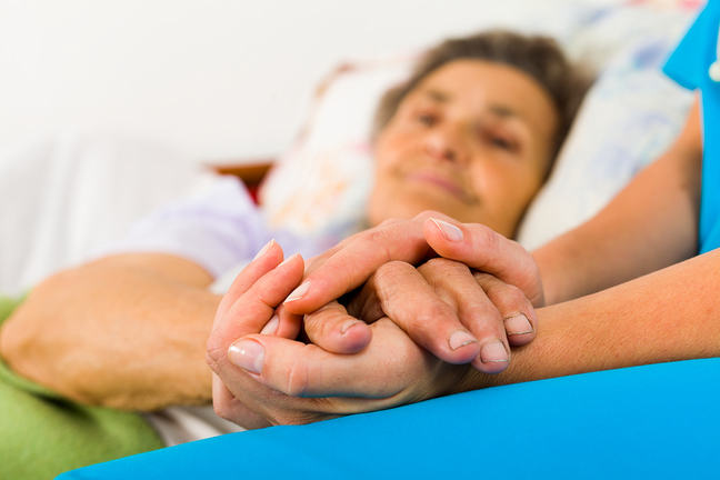 Nurse holding lady's hands in bed
