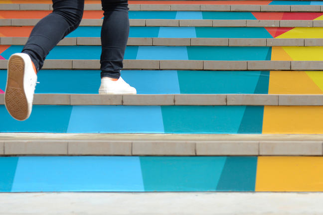 Teenage girl walking up colourful stairs