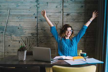 A woman sitting by a table with a computer and open books, putting her arms up in the air while smiling.