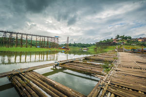 A rural bridge in Thailand, mid-construction over water with bamboo dock in foreground