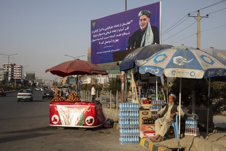 A roadside vendor goes about his business beside a Ghani campaign billboard in Kabul.