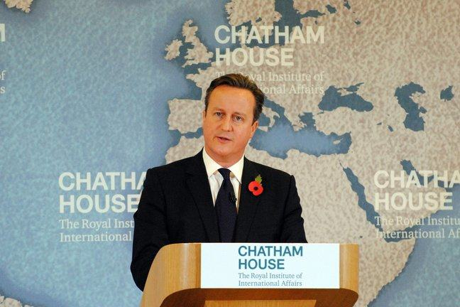 UK Prime Minister David Cameron standing a lectern at Chatham House giving a speech