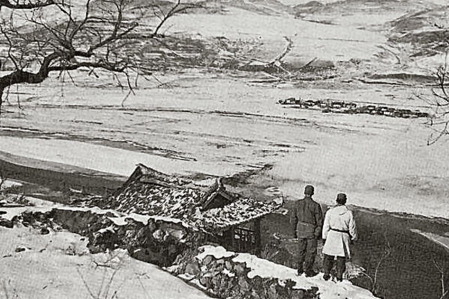 ON THE BANKS OF THE YALU, two soldiers look across the valley into the mountains of Manchuria.