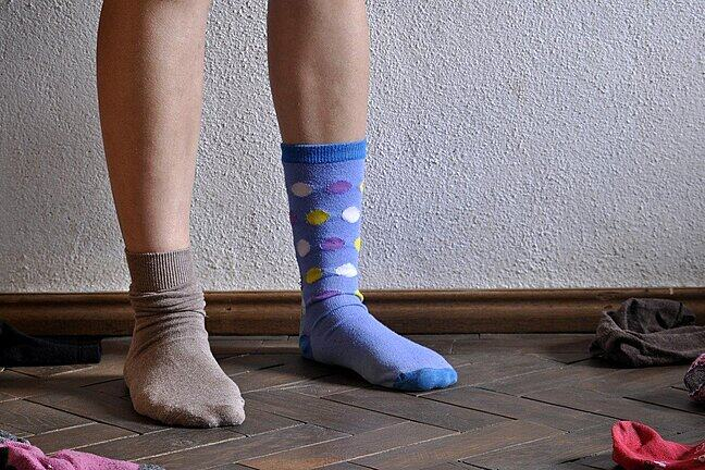 A person's feet, and they are wearing mismatched socks