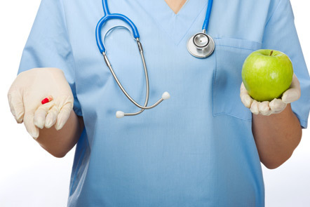Doctor presenting an apple and a pill.