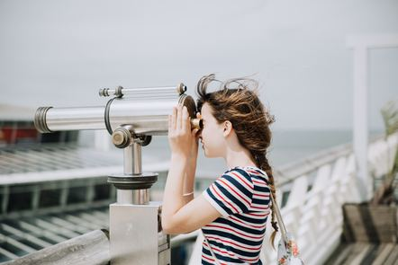 a girl looking through the lens of a pair of binoculars