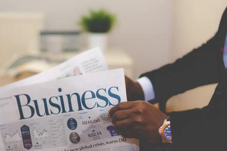 Businessman opening a newspaper