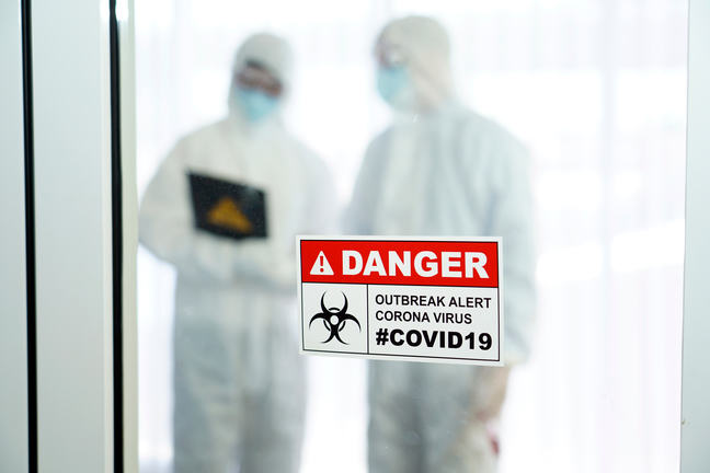 Outbreak alert Corona virus COVID-19, COVID19 signage in front of control area with doctors in personal protective equipment inside.