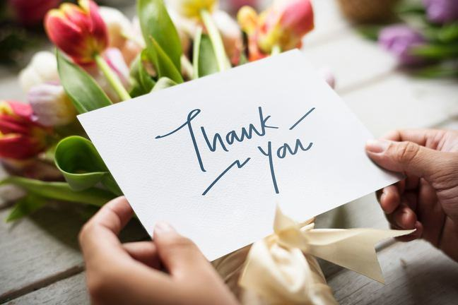 A woman's hands are holding a card that says in large blue written 'Thank You'. The card is being held over a bunch of colorful flowers with a cream ribbon tied around them.