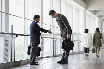An example of cultural miscommunication. Two colleagues meet in a corridor, one goes to shake hands whilst the other bows.