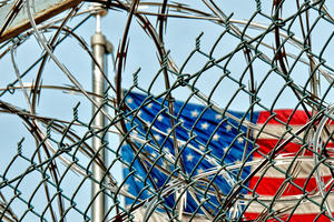 Prison detention fence with US flag in background