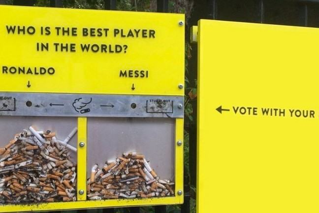 On a bright yellow background we see two clear containers containing cigarette butts, one labelled Ronaldo, the other Messi, with an overall title of 'Who is the best player in the world' and an instruction to 'Vote with your butt'.