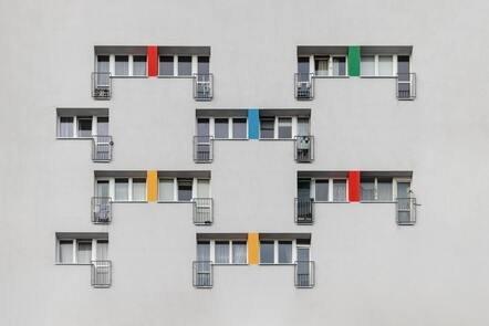 A photo of a block of flats. There are a few windows with colour squares painted around them.