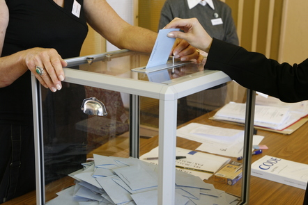 A woman posts her ballot paper into a clear ballot box during the 2007 French election.