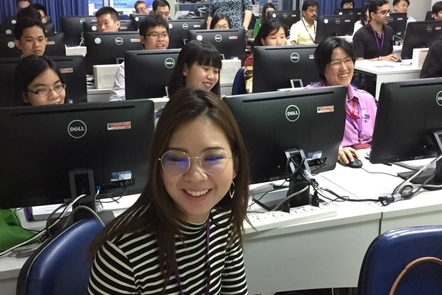 Learners seated and smiling looking up from their desktop computers in an IT training room: a woman in a deep red and white striped top is in the foreground, with rows of men and women at their computers and desks behind her.