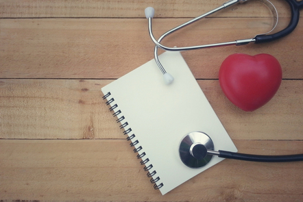 A notebook on a table with a stethoscope and plush heart