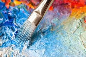 A painting brush mixing a colourful paint palette