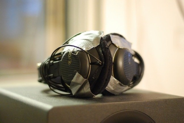 A pair of black headphones mended with ducked tape, placed on a black speaker.