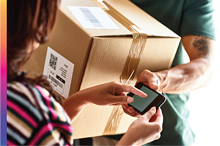 A man delivering a package to a woman, who is signing for the package on a mobile phone.