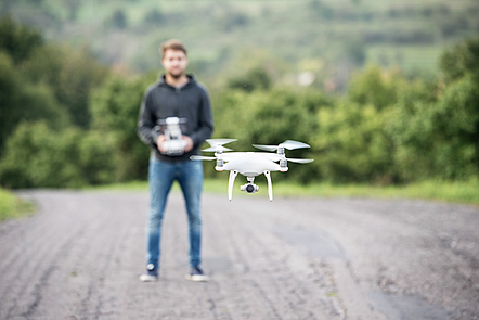 Young man with remote control and flying drone with camer