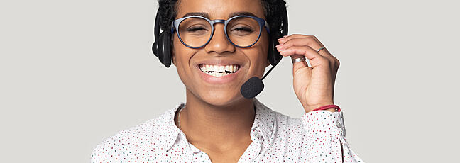 A woman of african ethnicity smiling and wearing a headset
