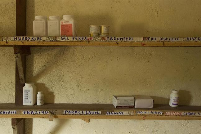 The shelves of village pharmacy are shown in this image. The shelves have a small supply of medication on them.