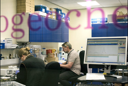 Two people working at a side bench in one of the stable isotope laboratories in Durham. A computer screen showing isotope data is visible.