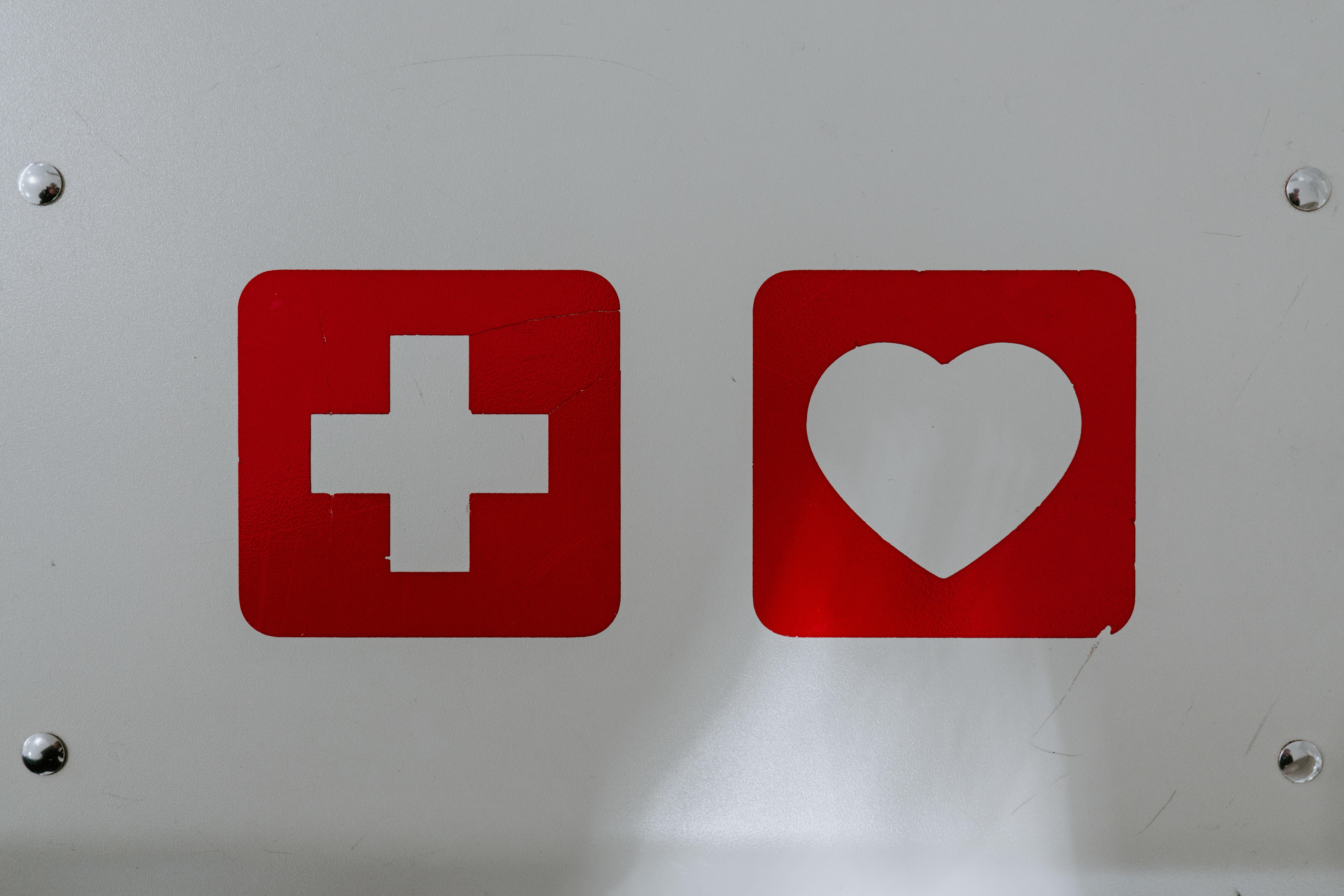 a medical sign and a heart symbol, red on white