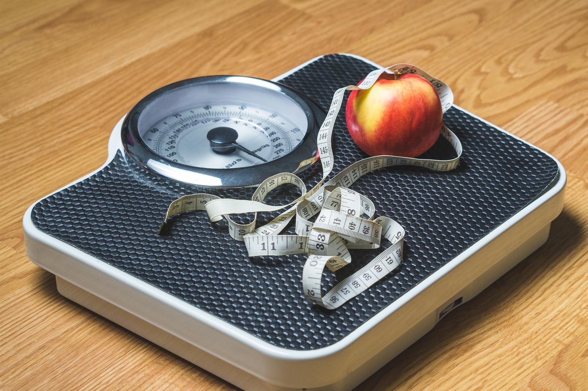 Weegschaal, meetlint en een appel