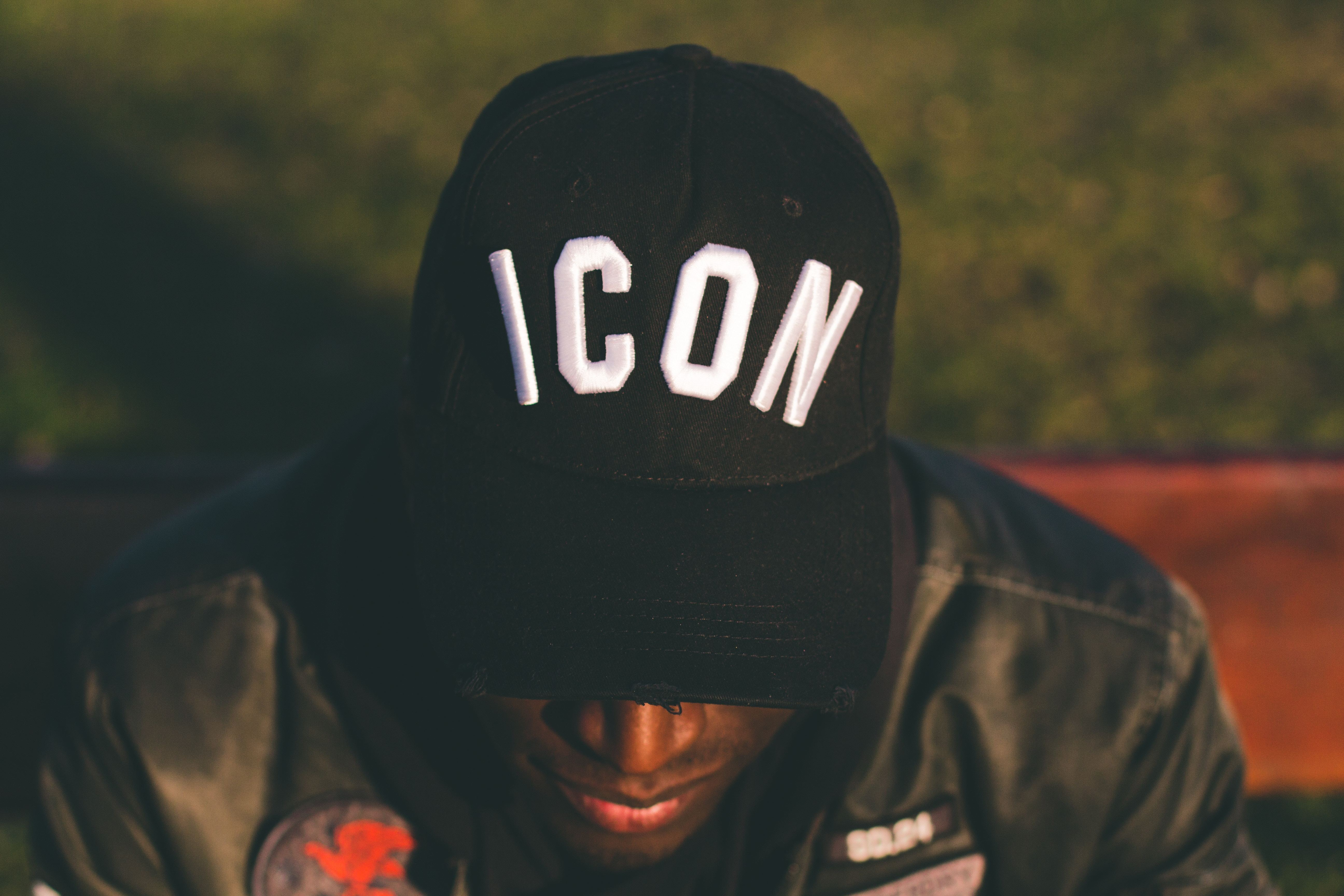 A close-up of a man in a baseball cap displaying the word 'Icon'.