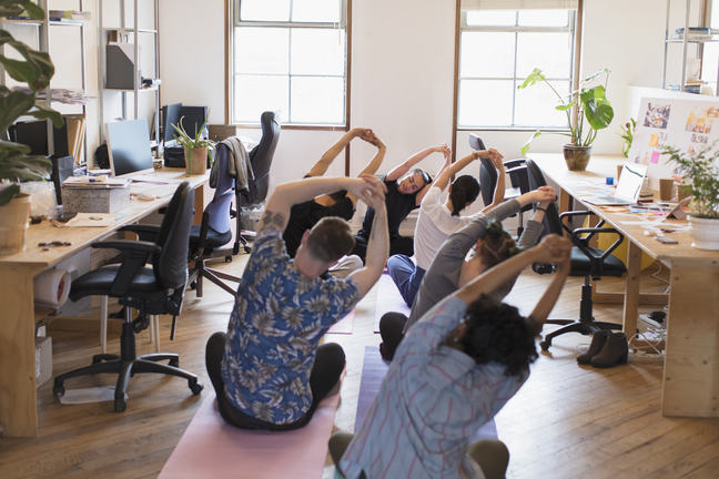 Creative business people stretching, practicing yoga in office