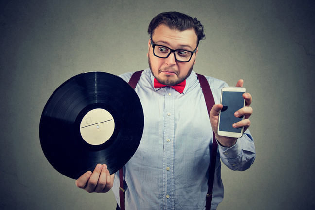 Man holding a vinyl record and a smartphone comparing new to old
