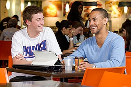 two students chatting with laptop
