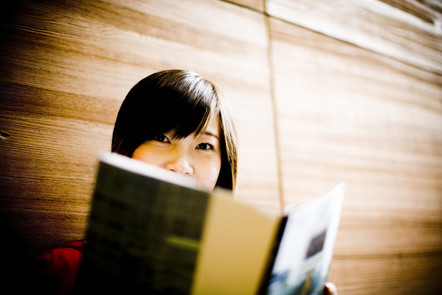 A smiling woman reading a book