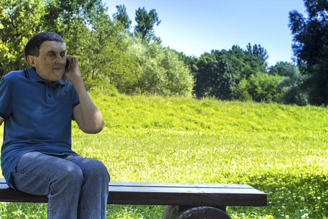 A man with an intellectual disability sitting on a bench talking on a mobile phone.