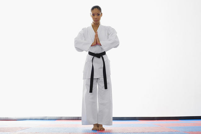 A young woman in all white karate attire with a black belt standing next to a white wall