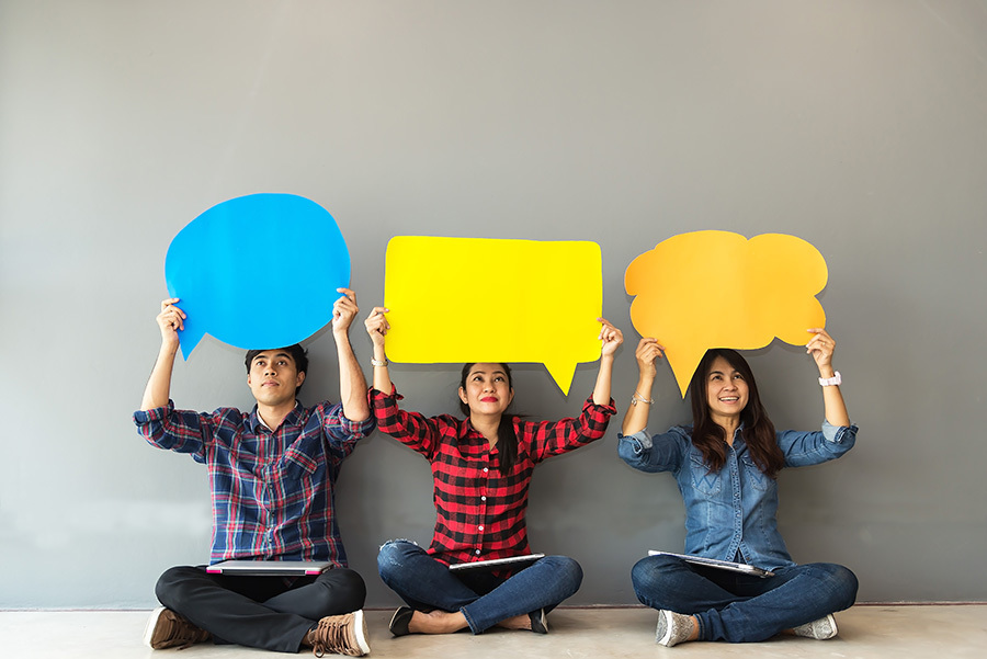Adult asian man and two women holding coloured paper speech bubbles above their heads.