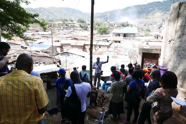 This image shows a group of learners in the foreground listening to a speaker on the edge of an informal settlement. Visible in the background are many houses, the majority of which have corrugated iron roofs.