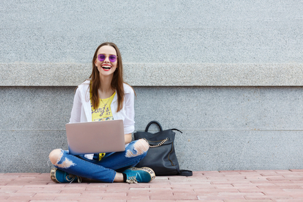 A woman smiling and laughing with her laptop.