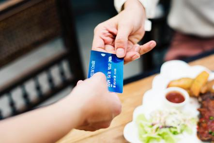 Two people holding credit card
