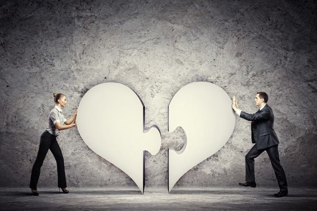man and women each with one half of a heart pushing the half towards each other