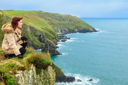 A woman looking out upon the landscape at the Cliffs of Moher.