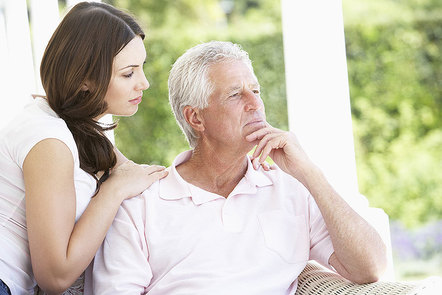 Older man looking pensive with younger woman hands on his shoulder
