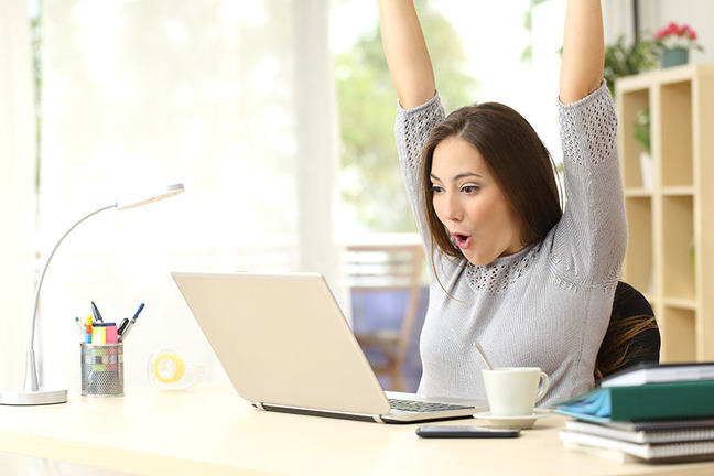 Woman behind her laptop cheering with her hands in the air